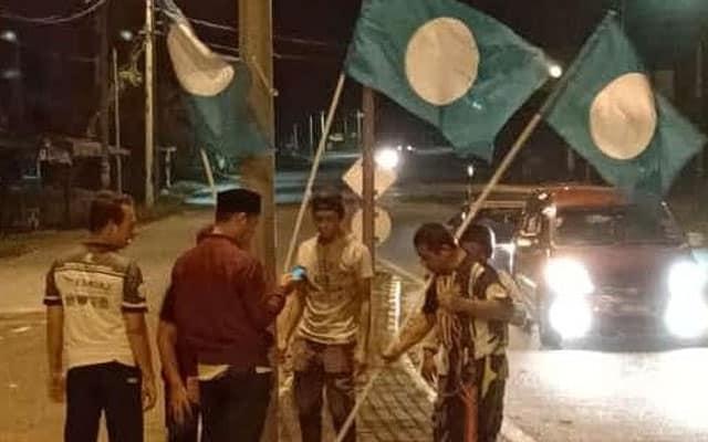 Tular gambar pemuda Pas bergotong royong pacak bendera ketika banjir sedang melanda